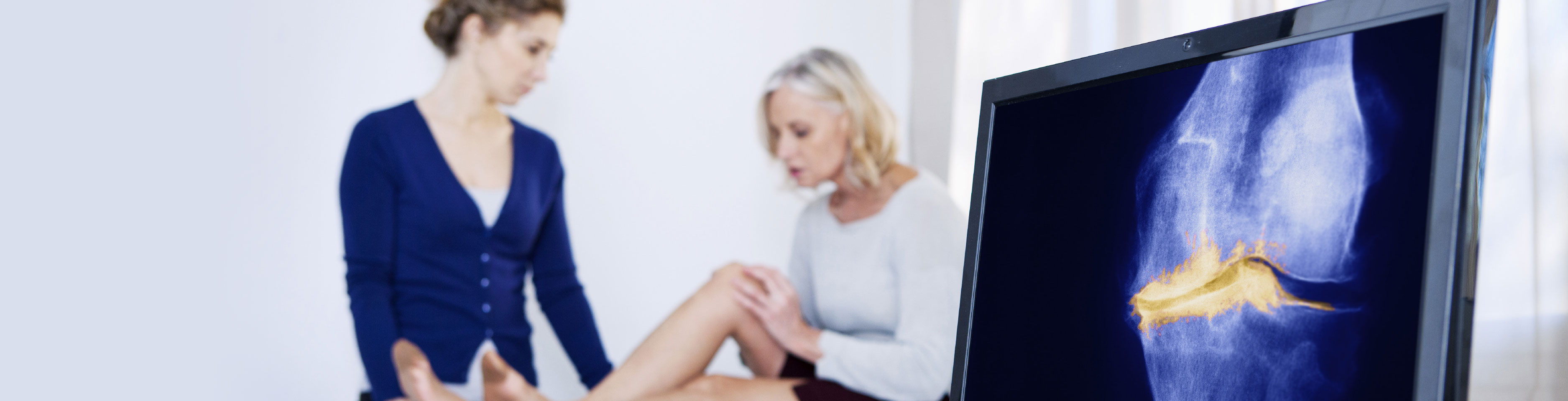 Doctor treats a patient and looks at scan of her leg