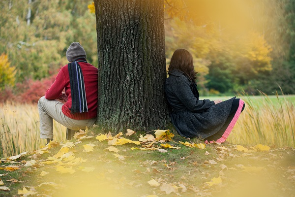 two young people sitting under tree