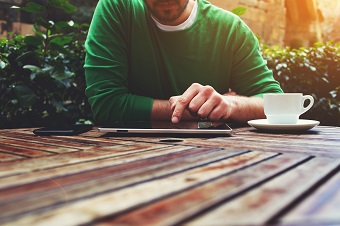 Man on ipad with coffee