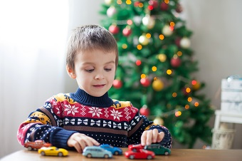Young boy playing with toy cars at Christmas
