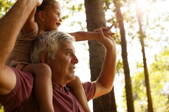 young girl sitting on grandpa's shoulders outdoors