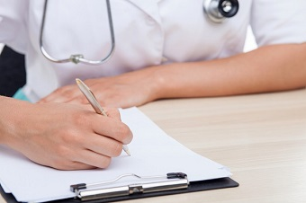 Health professional filling out paper form at desk
