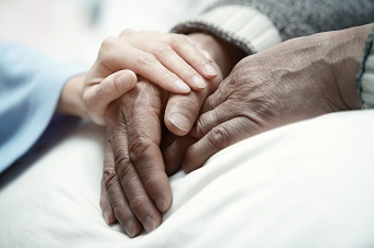 woman comforting elderly man in hospital or nursing home