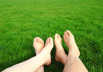 two people laying on the grass bare foot