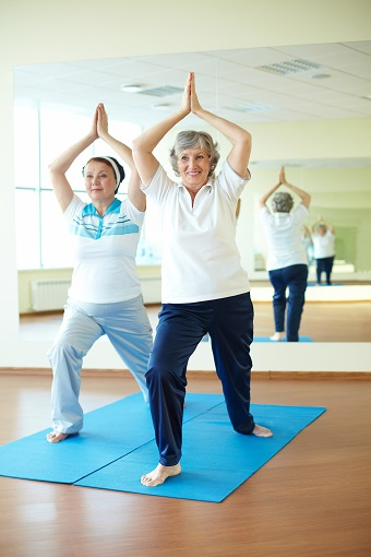 two elderly ladies practicing yoga in a studio