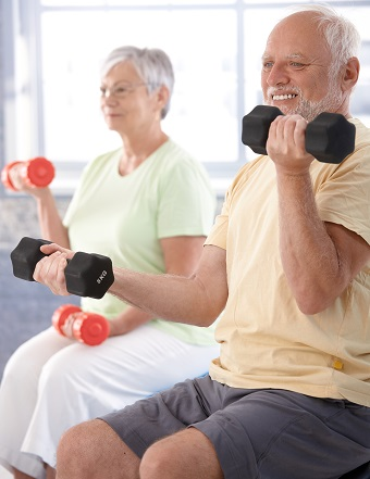 Two elderly people using weights at the gym