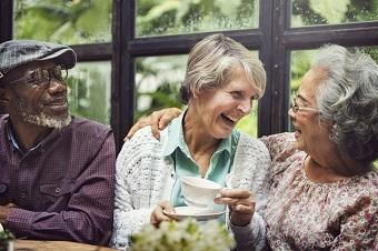 Three elderly people laughing and joking over tea