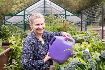 Older,Woman,With,Short,Grey,Hair,Watering,Abundant,Garden,With